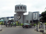 The main gate at the University of Ibadan, where I will be studying. Women dressed in traditional Yoruba clothing walking in front.